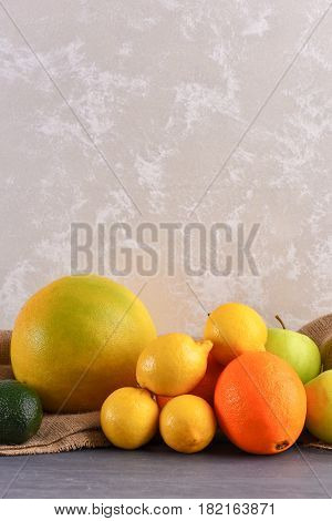 Various Fruits: Lemon, Apple, Orange, Avocado On Studio Wall Background