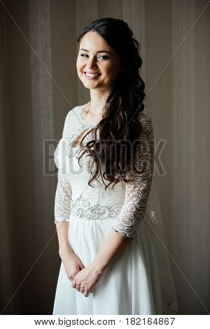 Beautiful young smiling bride in white dress waiting for the groom indoors. Elegant charming young brunette bride is posing indoors in a wedding dress. Morning the bride