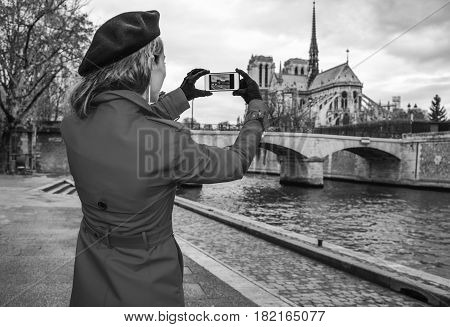 Traveller Woman On Embankment In Paris Taking Photo With Phone