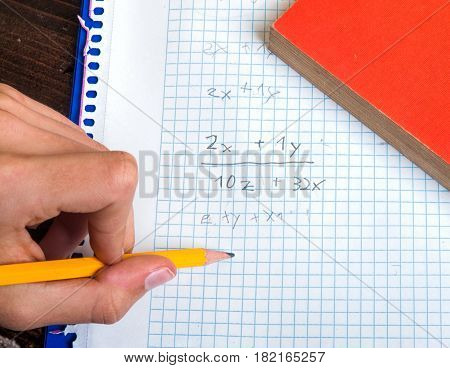 Hand holding pencil and doing mathematics on paper