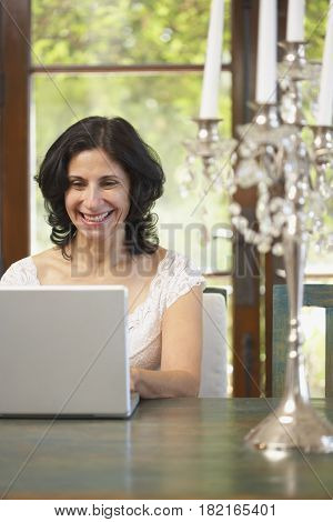 Confident Middle Eastern woman typing on laptop in dining room
