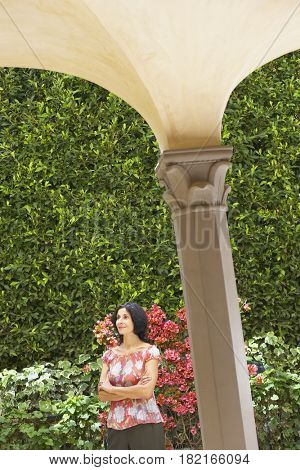 Confident Middle Eastern woman standing in garden