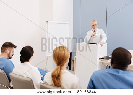 Enjoying anatomy lecture. Delighted bearded aged professor working and giving the lecture to the students in the university while explaining anatomy details