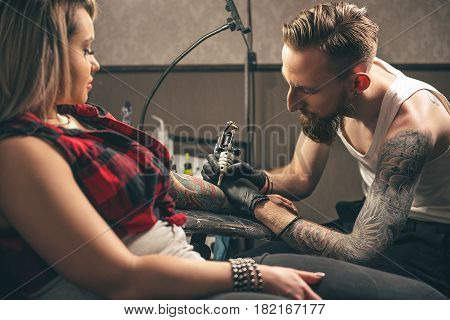 Side view portrait of calm bearded male artist drawing image on female arm. She sitting opposite him