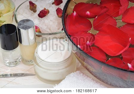 Accessories for manicure: hand bath with rose petals, essentials oils,  bath salt, towels, cream, nail polish, scissors, nail file. Beauty and spa concept