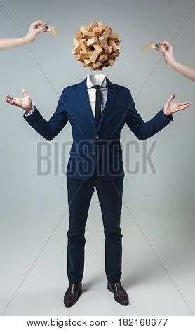 Businessman with wooden game box instead of head on gray studio background.