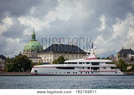 Copenhagen Denmark - July 29 2015: Large modern luxury yacht anchored in harbor of Copenhagen in front of on Amalienborg and Marble church.