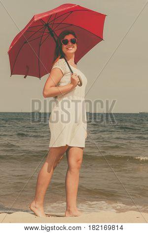 Redhead Woman Walking On Beach Holding Umbrella
