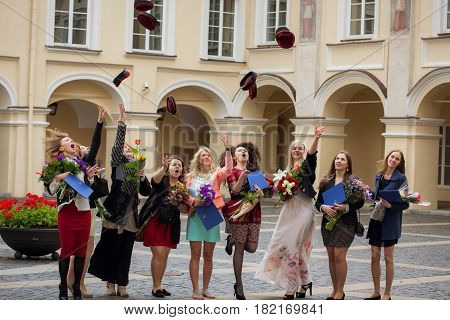 Vilnius Lithuania - June 18 2014: Students of Vilnius University are throwing their head-wear during student graduation ceremony in the courtyard of the university.
