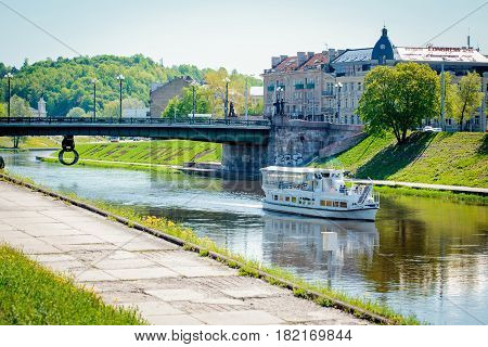 Vilnius Lithuania - May 9 2015: Ship in the Neris river and sculpture 'Chain' by sculptor Kunotas Vildziunas under the Green bridge in Vilnius.