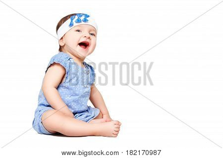 Laughing cute little girl sitting isolated on white background