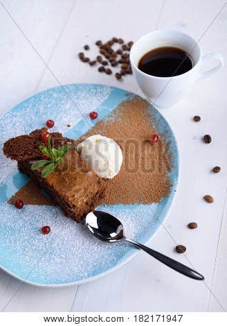 Chocolate brownie with ice cream on a blue plate next to a cup of coffee