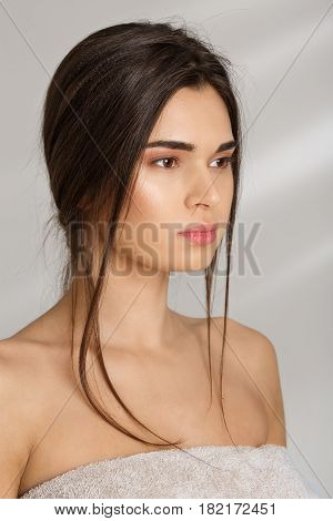 Side view. Closeup portrait of beautiful woman covering herself with towel, isolated on grey.