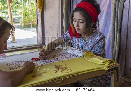 MARGILAN UZBEKISTAN - AUGUST 20: Woman embroidering fabric by hand with traditional Uzbek patterns in a silk factory workshop. August 2016