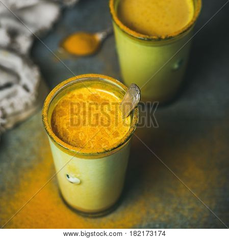 Golden milk with turmeric powder in glasses over dark background, copy space, square crop. Health and energy boosting, flu remedy, natural cold fighting drink. Clean eating, detox, weight loss concept