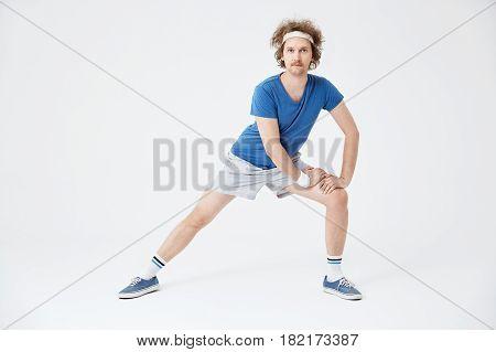 Man marming up. Blue t-shirt, long white socks, grey shorts, white headband, looking concentrated