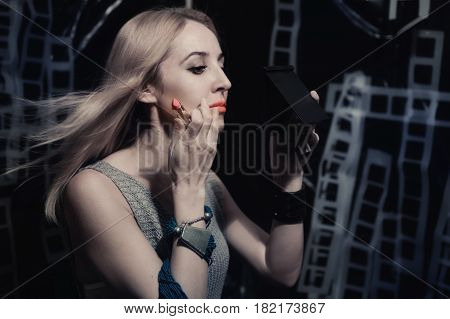 Young woman paints lips with pink lipstick. Studio portrait profile