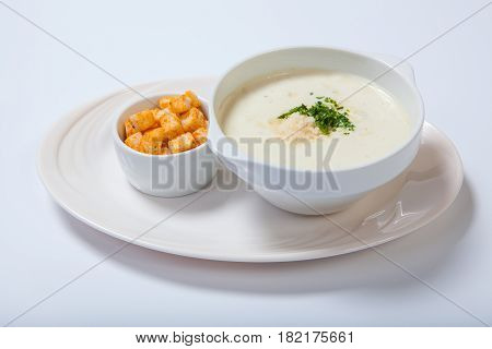 Delicious Creamy Soup With Parsley, Croutons And Cheese On White Dish