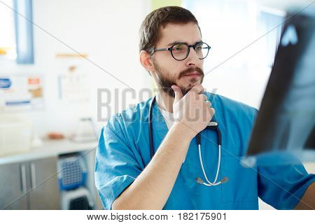 Pensive ragiologist looking at x-ray image