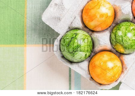 Colored eggs in box on colored table .