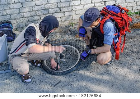Yalutorovsk, Russia - May 27, 2006: Men repairing bicycle with flat tire