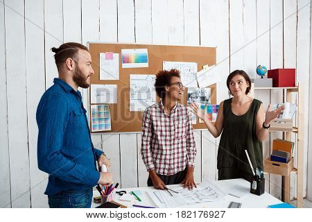 Colleagues smiling, speaking, discussing drawings, new ideas in office
