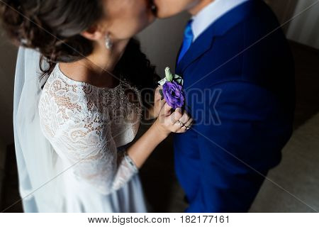 Boutonniere in the bride's hands. Bride inserting boutonniere