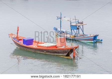 Two blue and red vacant fisherman's rowboats floating on sea traditional fishing in Thailand.