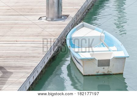 White and blue rowboat anchored at the sea dock.