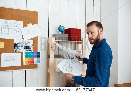 Young successful architector smiling, holding drawings, standing in office.