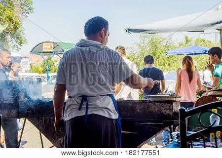FERGANA UZBEKISTAN - AUGUST 20: Man grilling meat skewers called shashlyk in a restaurant in Fergana. August 2016