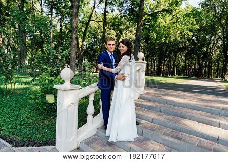 The bride and groom stand on the stairs in the park. The bridegroom embraces the bride. Wedding couple in love at wedding day