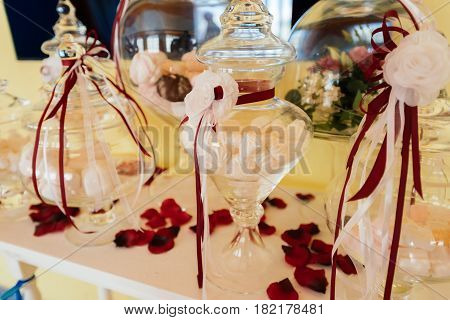 Holiday candy bar. Zephyr in a glass vase decorated with flowers and ribbons on the dining table