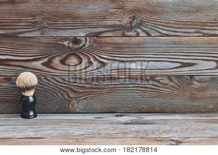 Classic shaving brush on old wooden background with copy space