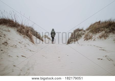 Woman wolking on the empty beach in winter time