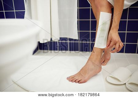 Young woman making depilation of legs with wax strips in bathroom