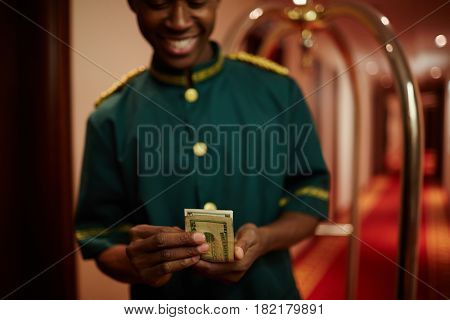 Young hotel porter counting dollars
