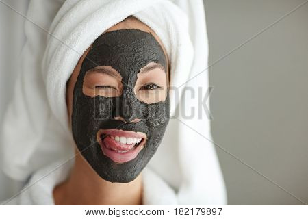 Flirty girl winking while having purifying mask