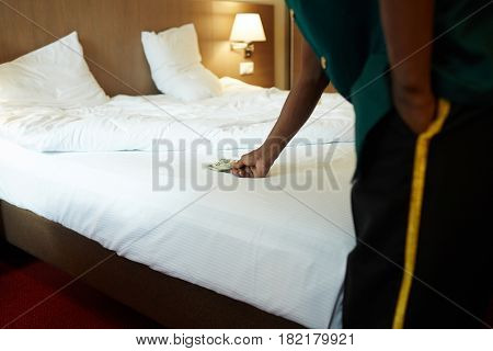 Hotel bellman taking tips from bed
