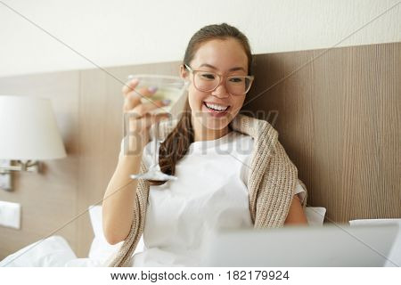 Happy female with glass of martini networking in bed
