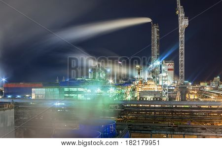 Steam from the cooling tower against the background of a pipeline and a chemical plant at night