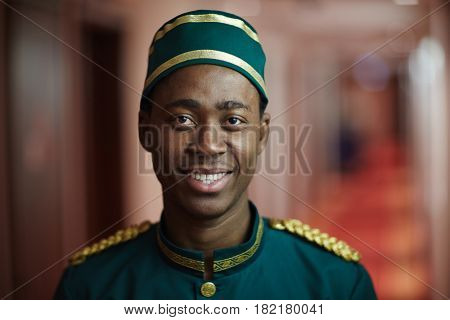 Happy young hotel porter in uniform looking at camera