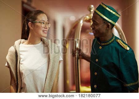 Hospitable porter talking to young tourist in aisle of hotel