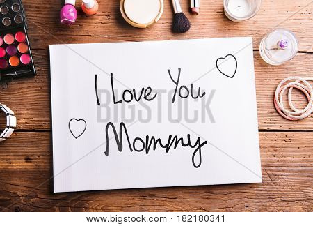 Mothers day composition. I love you Mommy note. Various beauty products laid on table. Studio shot on wooden background. Flat lay.