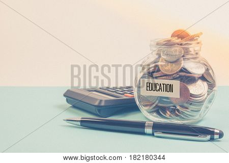 Money Saving For Education Fee Or School Free In The Glass Bottle With Pen On Blue Background In Pas