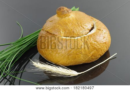 empty bread bowl with a lid on dark background