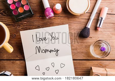 Mothers day composition. Greeting card laid on table and various make up products. Studio shot on wooden background. Flat lay.