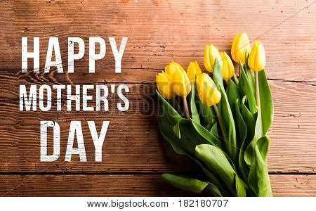 Mothers day composition. Happy mothers day note and bouquet of yellow tulips. Studio shot on wooden background. Flat lay.