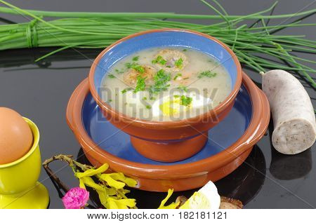 sour soup in dish with sausage and egg