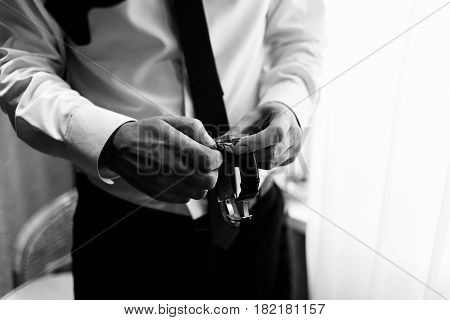 The watch is in the hands of a man. Men's watches on the arm. Men's hands with a watch. Black and white photo